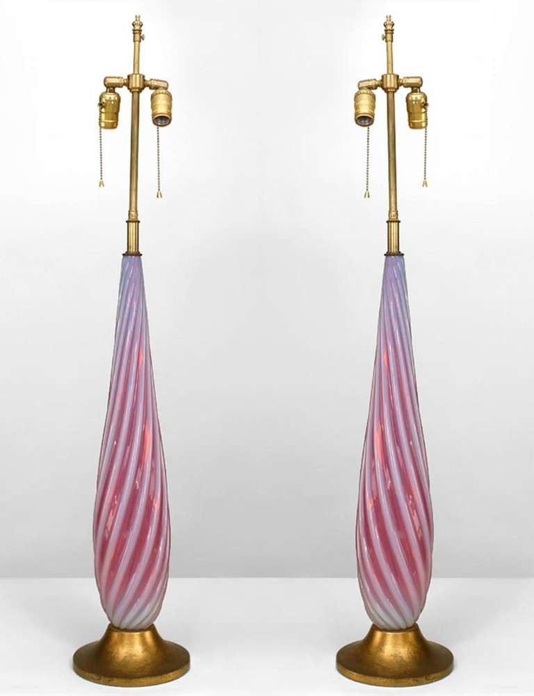 Pair of Italian 1940s Venetian Murano red and white Murano glass table lamps with swirl design and mounted on a round gilt wood base (PRICED AS Pair).