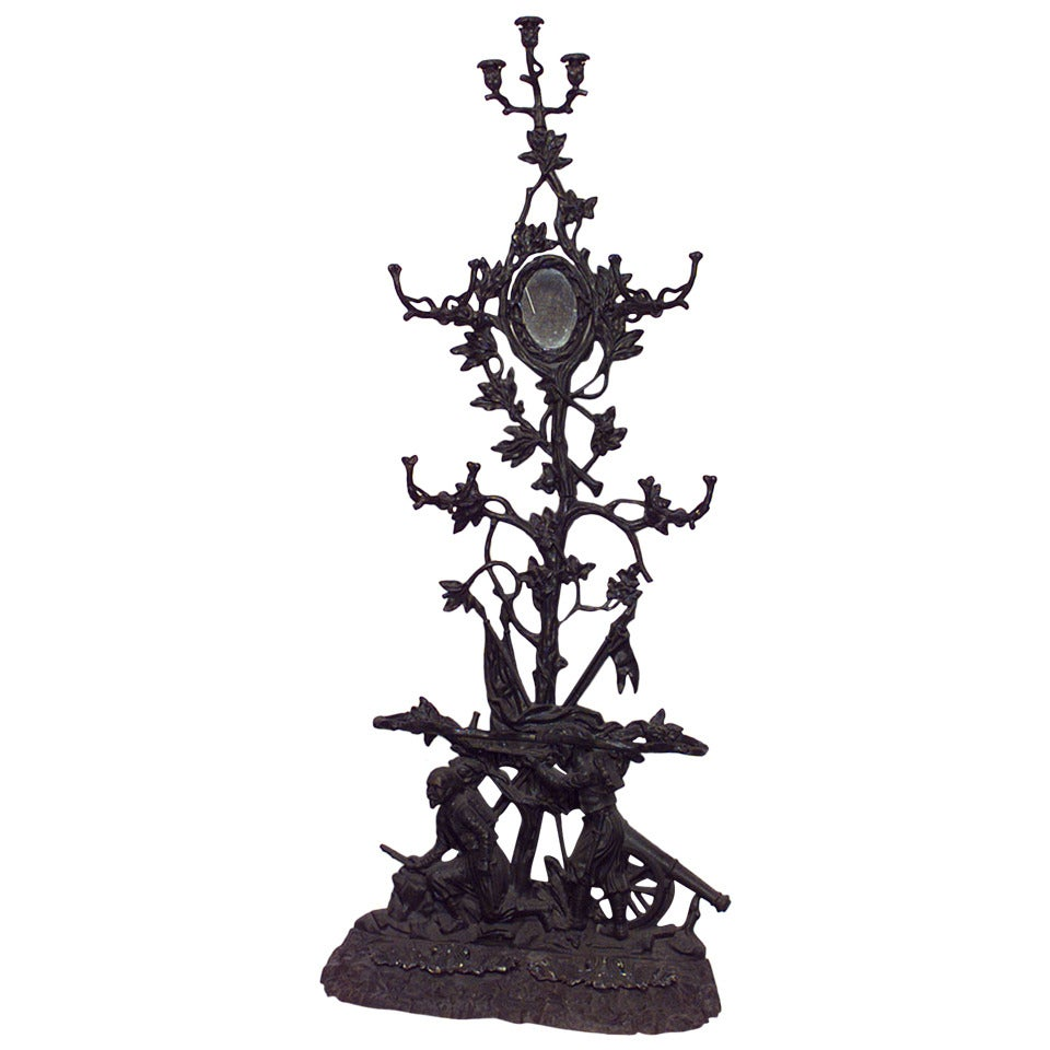 Nineteenth century French hatrack signed by the Corneau Freres of Charleville. The piece is composed of wrought iron cast in imitation of carved wood with leaf-like hooks surrounding a round mirror above a naturalistic base with two figures