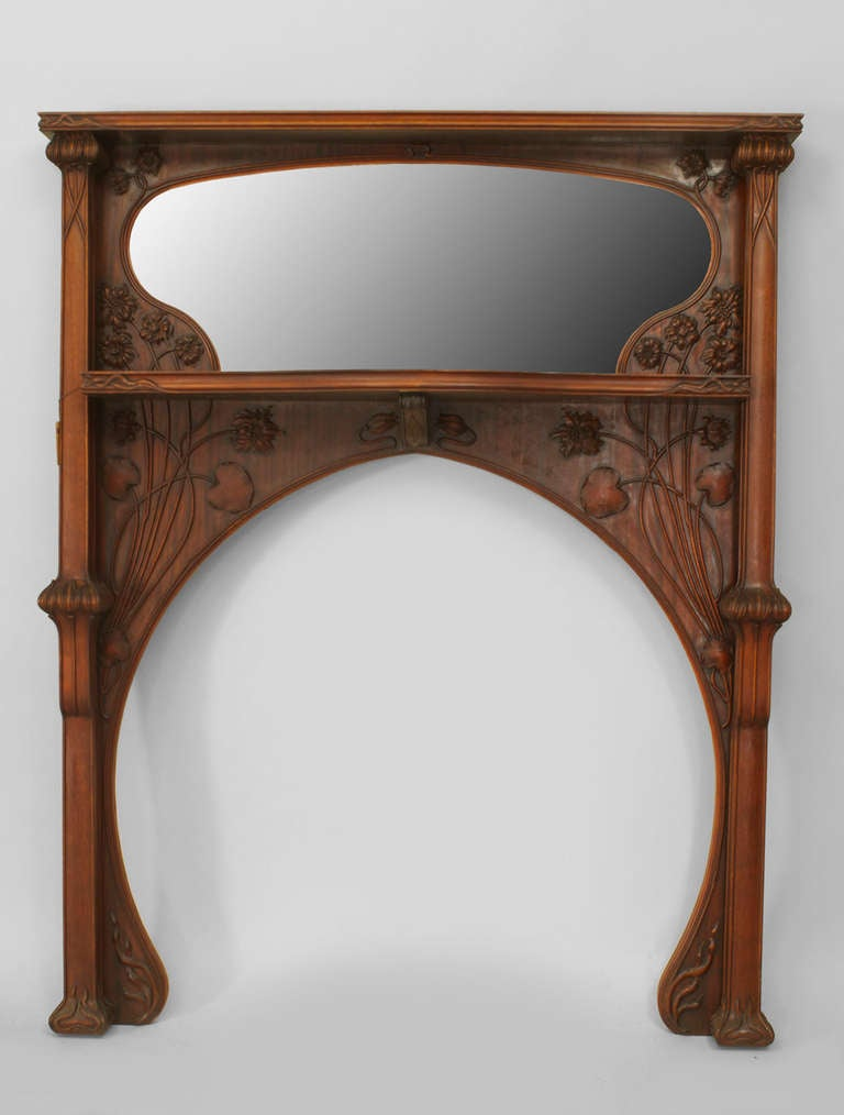 Attributed to French Art Nouveau designer Louis Majorelle, this fireplace mantel is composed of mahogany carved with sinuous floral motifs around an arched cutout and an upper tier inset with an irregularly shaped pane of mirrored glass.