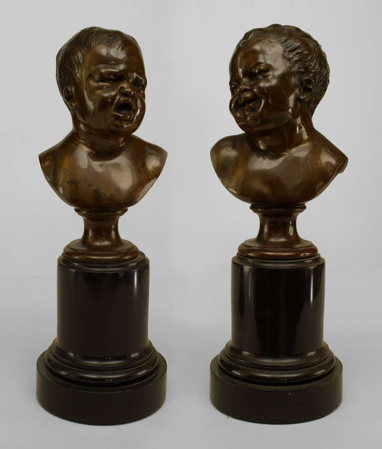 Pair of 19th century French left and right bronze busts depicting two babies, one laughing and one in tears, upon round black marble pedestal bases.