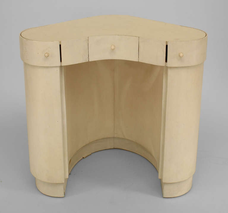 Italian Art Deco ladies dressing table veneered in white parchment with a closed, curved triangular design featuring one small central drawer and two side cabinets with concealed shelving.
