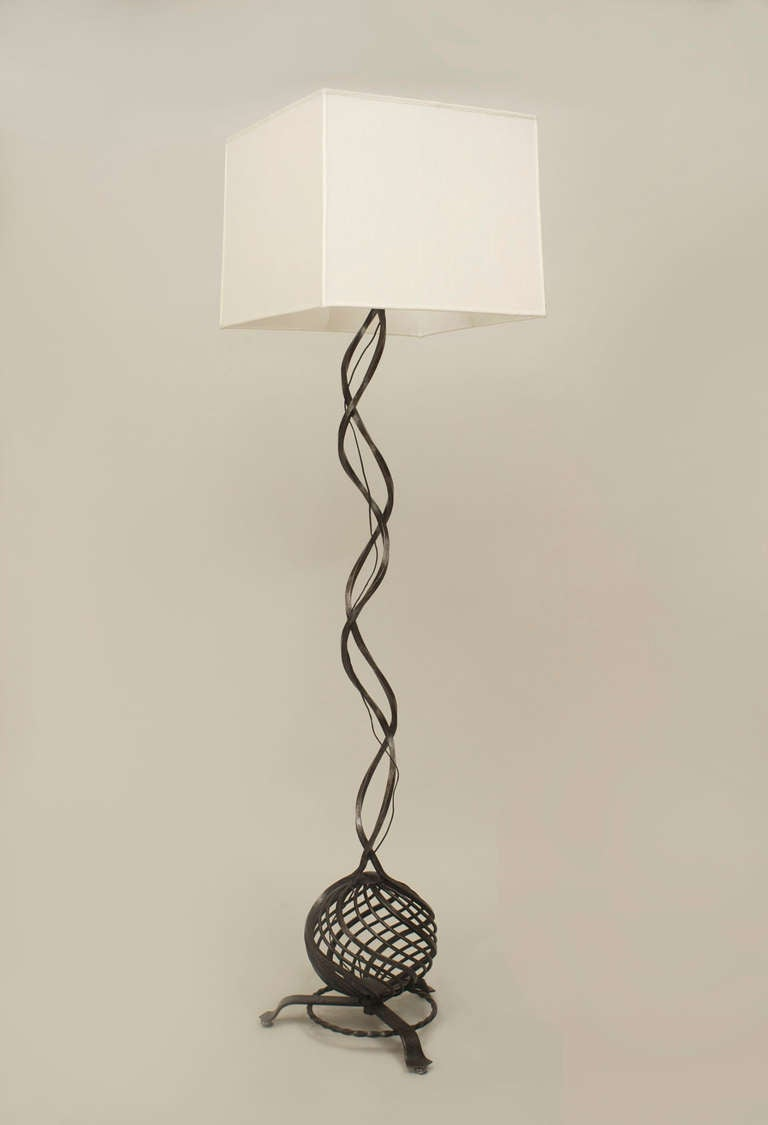 French Art Deco wrought iron floor lamp topped with a square white shade which rests upon a swirl design base composed of two interwoven shafts terminating in a latticed sphere base and three short legs.