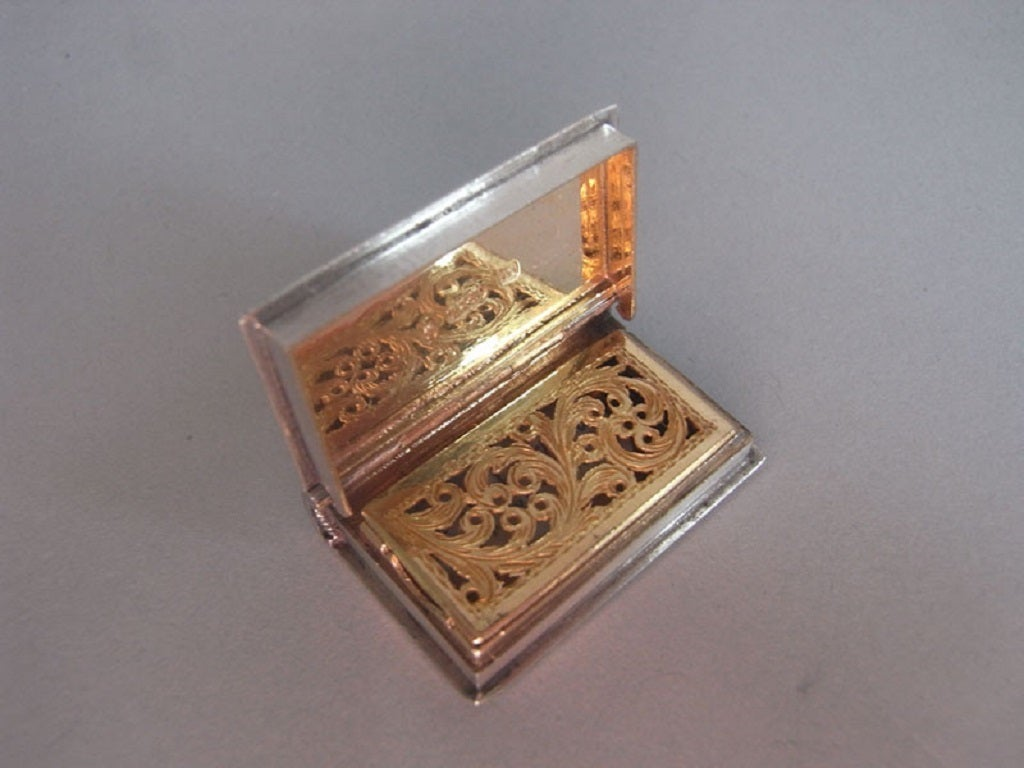 The vinaigrette is of narrow rectangular form and is modelled to simulate a book. This example has a reeded spine and is engraved on the cover and base with tartan pattern. The cover also displays a rectangular cartouche engraved with script