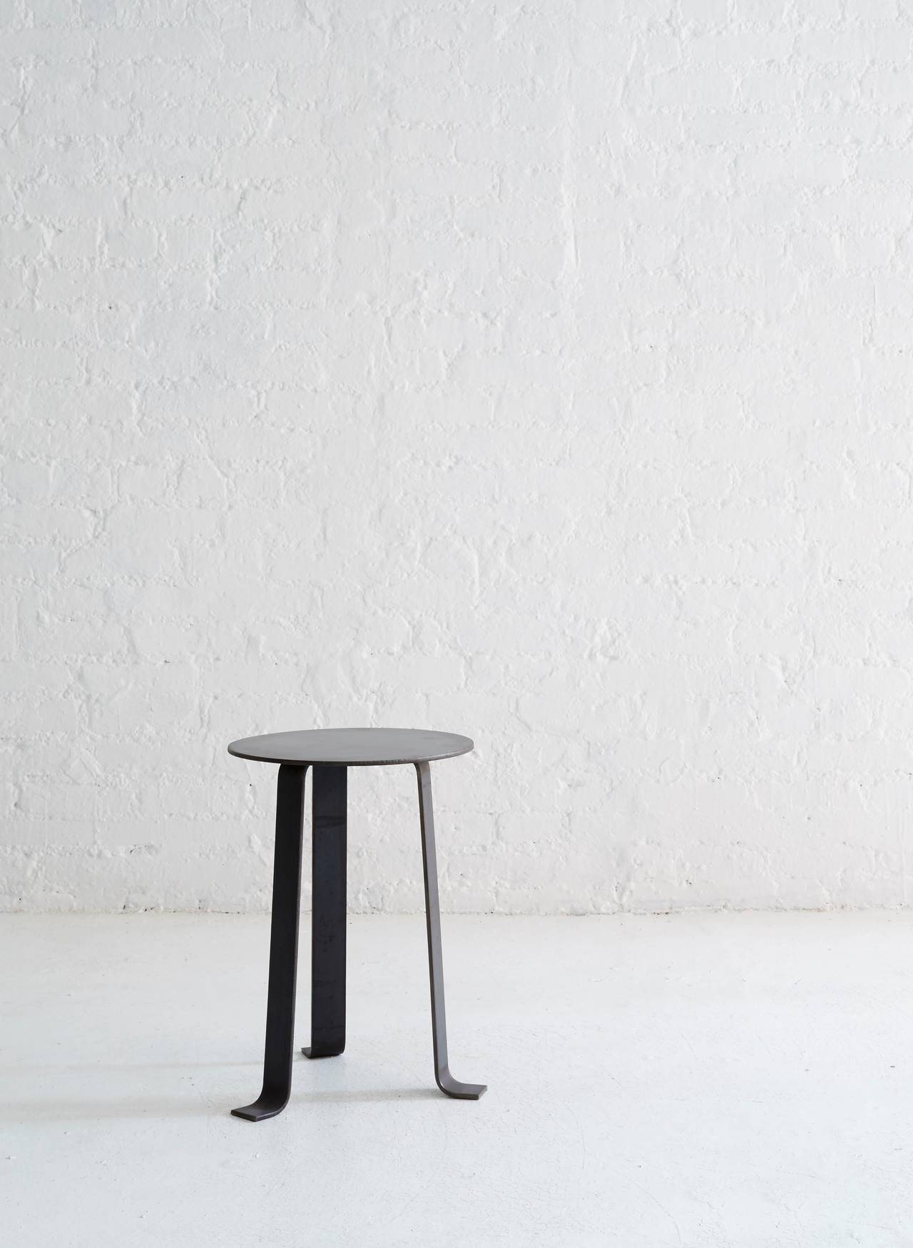 """The steel tripod stool has a classic silhouette, modernized in steel with design influences from Ignazio Gardella's """"Digamma"""" chair and Charlotte Perriand's """"Ombra Tokyo"""" chair.  Available in four finishes: Raw steel. Black"""