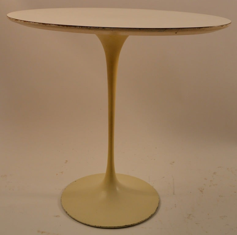 Vintage original Saarinen for Knoll oval tulip table. Cast iron base with white laminate top. This example shows some cosmetic wear normal and consistent with age.
