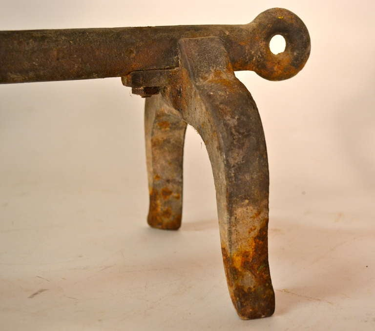 Pair of solid iron andirons of arrow form, with original rust surface.