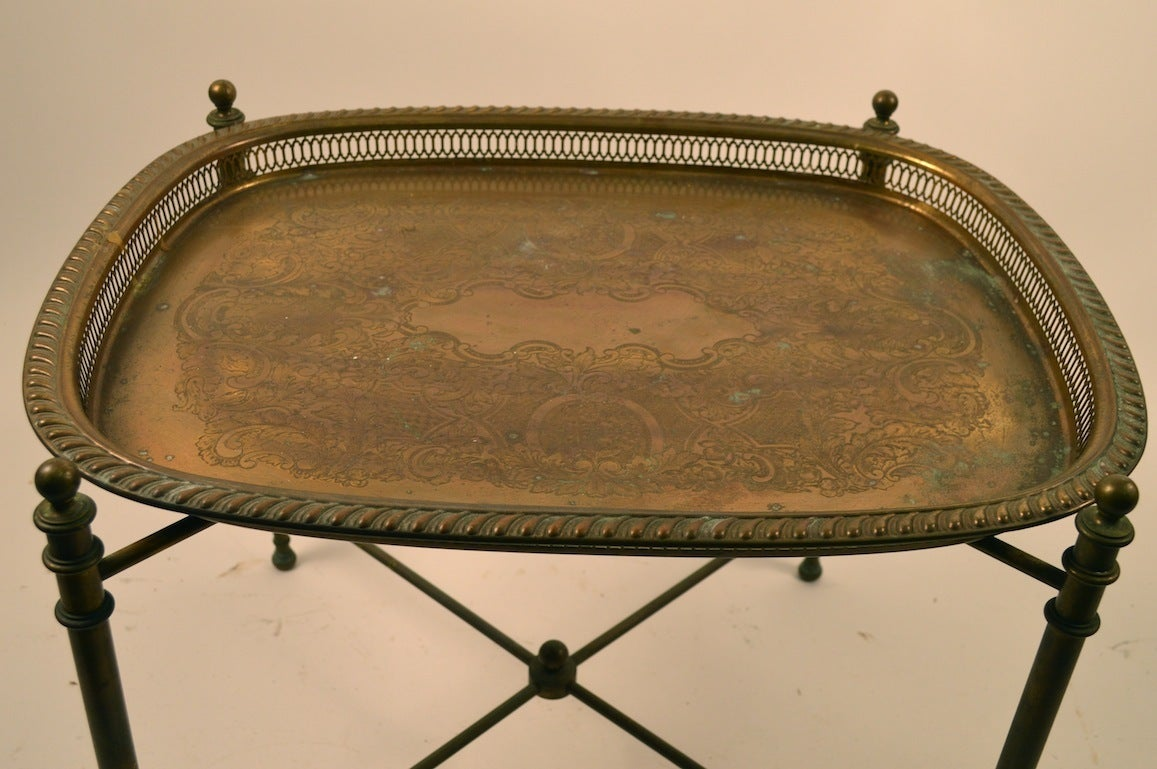 Removable tray top rests on solid brass frame. Tray has pierced gallery edge, and etched medallion design.