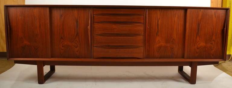 Danish Modern Server,  Sideboard, Credenza  - five center drawers flanked on either side by sliding doors, which open to shelves. The whole case rests on front to back sled style legs. Fine original condition, with onlt the expected normal wear,