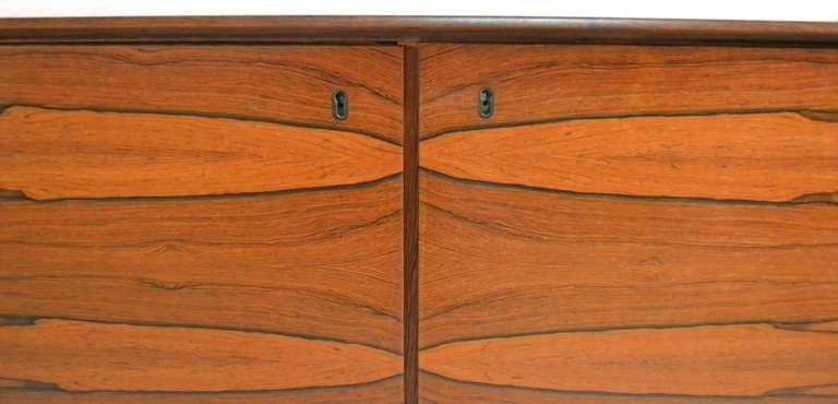 Danish Modern Rosewood server with matched veneer. Four doors open to revel shelving storage space. This server is in fine original condition, original finish, and still retains the original keys for the locking doors.
