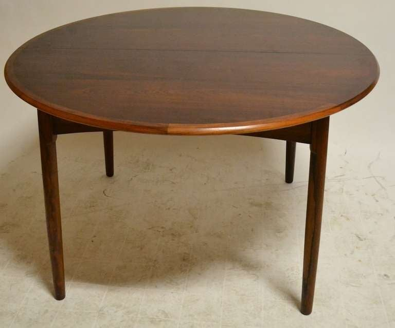 this round danish modern rosewood dining table with two leaves is no