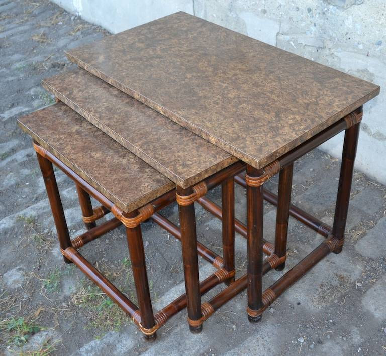 Three nesting tables of graduated size, each with wood legs, and formica faux finish top. Dimensions in listing are for the largest of the three.