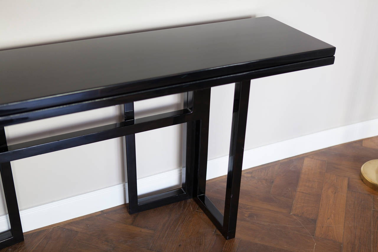 Very elegant Console - Table by Maison Jansen, France circa 1970, black lacquered wood, folding system from a console to a table, brass hinges Length 170 cm, height 79 cm, depth 40 cm, folding depth 80 cm. Perfect condition!