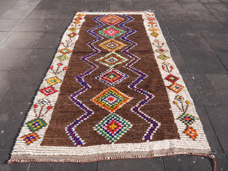 Rare vintage example of tribal moroccan art. Beautiful brown field contrasting with wool white border showing flowers.