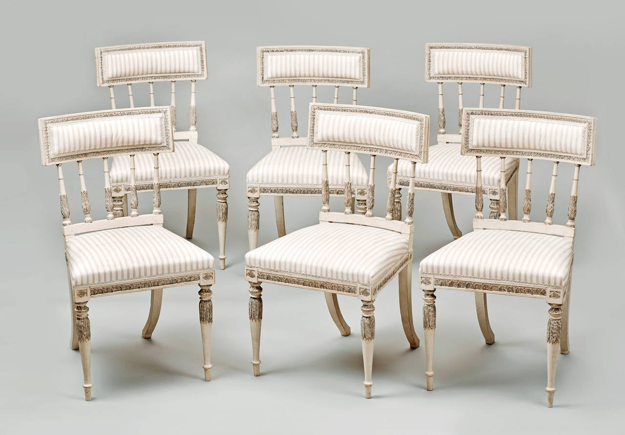 An elegant set of six Swedish Gustavian dining chairs from the neoclassical period painted in cream white and grey, with leaf tip carvings overall. The front round tapering legs with leaf carving, to the back sabre legs. Upholstered seat and back