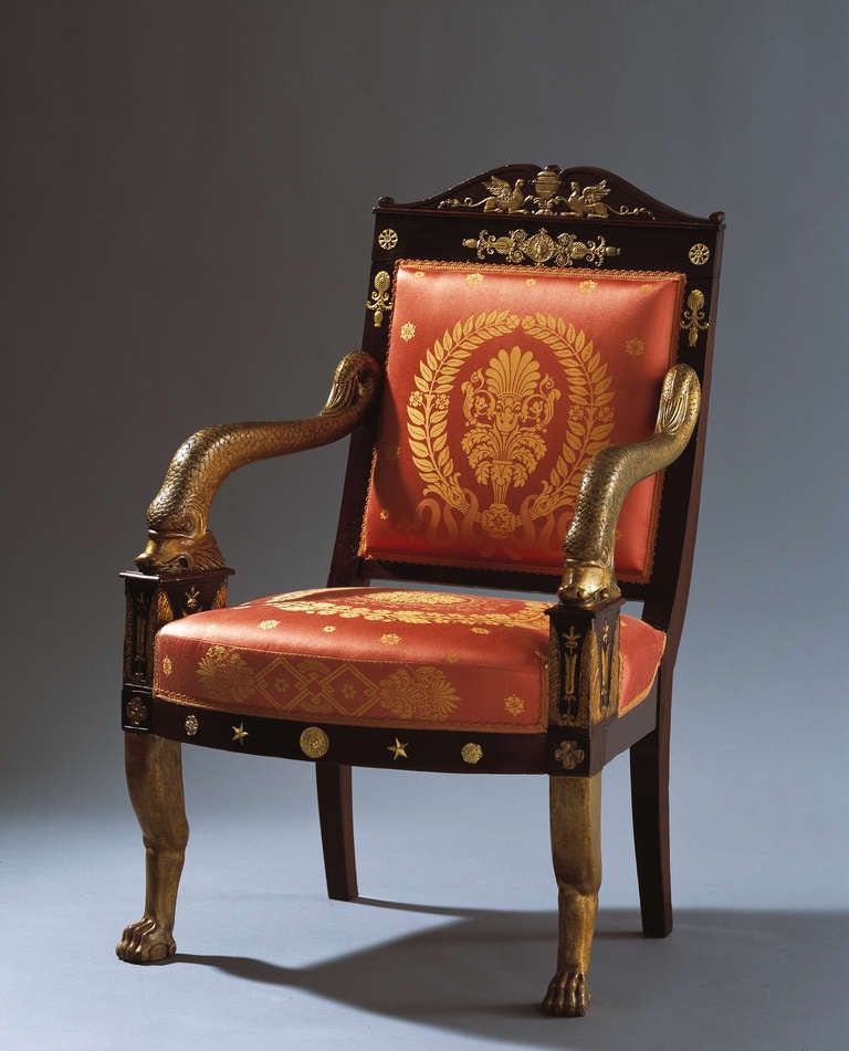 An impressive Napoléonic Empire mahogany armchair, attributed to Jacob-Desmalter (1770-1841). With a pedimented top rail above a rectangular padded back and seat covered in red and gold silk, beautifully carved and gilded dolphin arm supports, the
