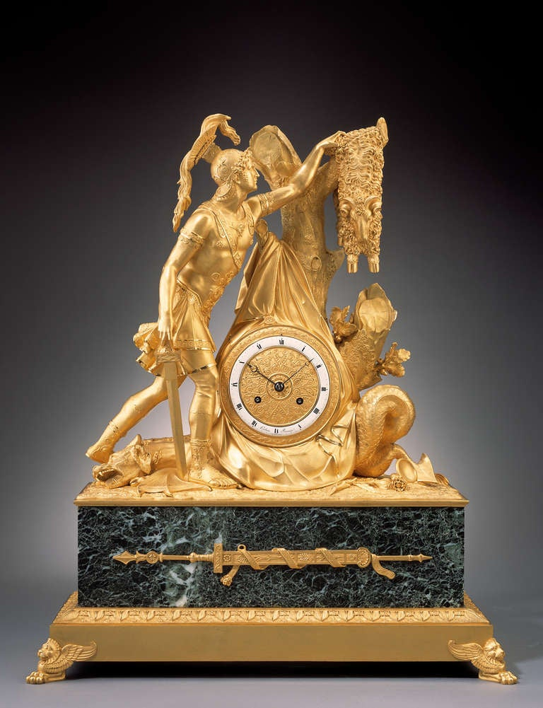 Depicting Jason capturing the Golden Fleece, the young warrior reaching into a tree branch for the fleece with the slain hydra at his feet, the tree centring the ormolu dial with Roman chapter ring, on a rectangular base with animal paw feet. The