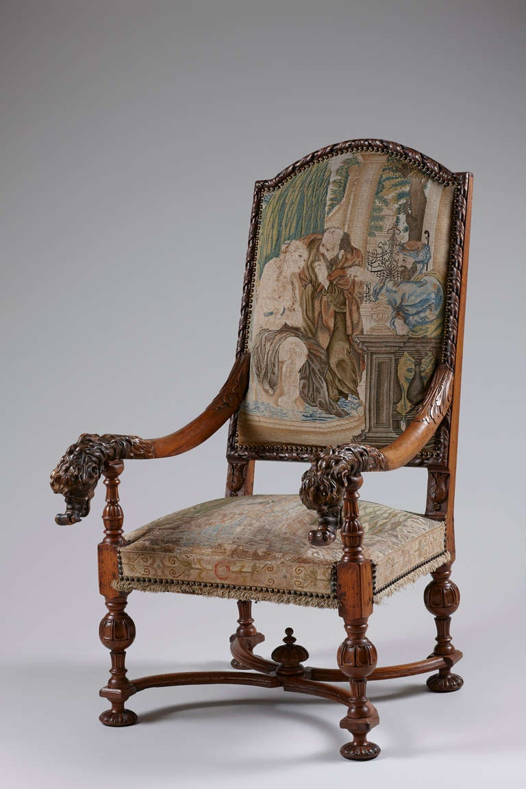 Fine tall German late 17th century Baroque walnut throne armchair with a rectangular arched padded back and seat covered in 17th century Gobelin depicting 'Susanna and the Elders' with fringed edge, flanked by downscrolled foliate-carved armrests