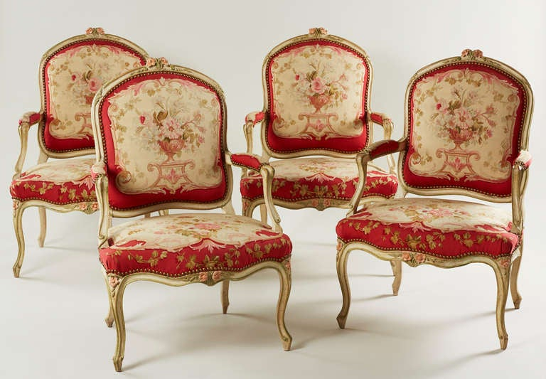 A rare and attractive set of four period Louis XV pale green and rose painted armchairs. Each with a flowerhead and foliate carved toprail, padded and scrolled arms and a serpentine seat, upholstered in brass studded 19th century Aubusson style