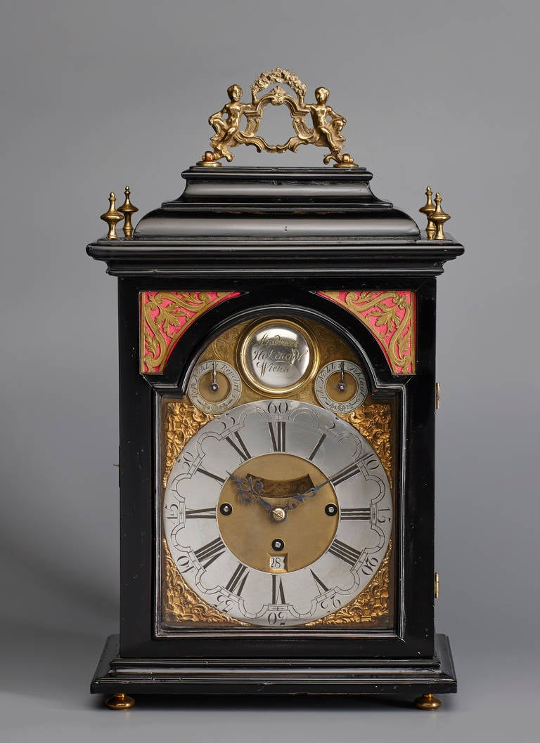 An attractive Austrian mid-18th century Baroque period quarter-striking bracket clock by the maker Andreas Hohenadl, Vienna. The ebonized fruitwood case with figurative brass carrying handle to the inverted bell top, arched glazed viewing apertures