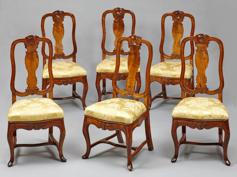 Set of six 18th century German Baroque walnut dining chairs, probably from Saxony. With baluster shape splat and drop in seat covered in yellow silk (modern). The seat rail and back with central carved foliate spray and acanthus leave. On cabriole