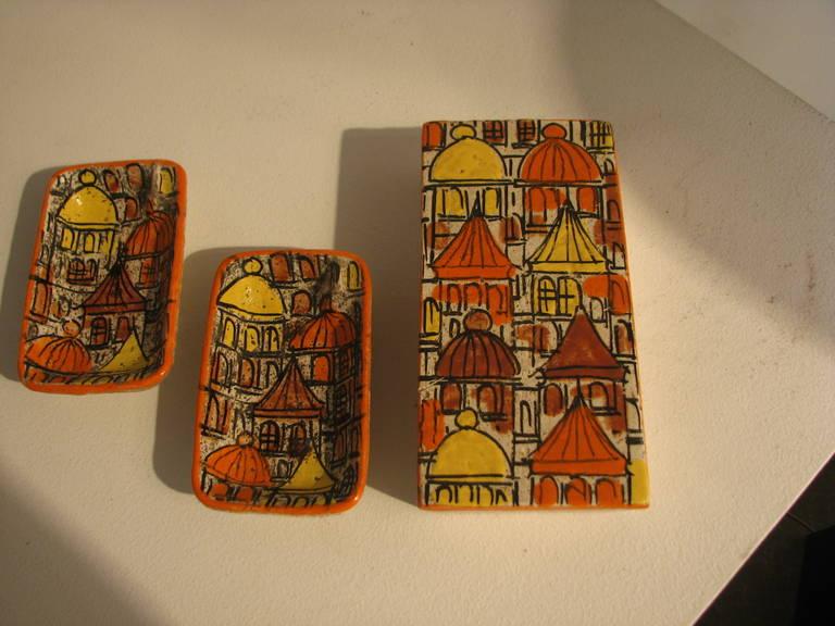 "Raymor three-piece ceramic cigarette box and ashtray set Measures: Box - 8"" W x 4"" D x 2"" H Ashtrays - each 5.5"" W x3.5"" D x 2"" H."