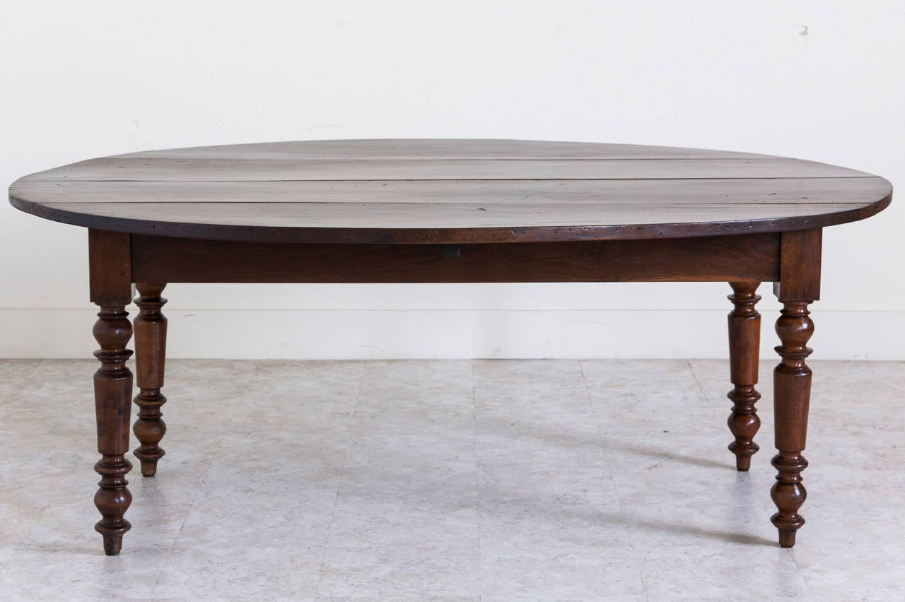 The deep hued walnut of this unusually large oval farm table contributes to its warm and welcoming presence. This piece is made entirely of solid walnut and is all hand pegged with beautifully turned thick legs and drop leaves. Easily seats eight