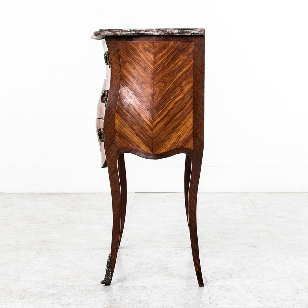 This small-scale 18th century rosewood marquetry Louis XV chest of drawers features its original bronze hardware and a very unusual lavender hued marble top. With serpentine curved sides, three drawers and delicate cabriole legs leading to bronze