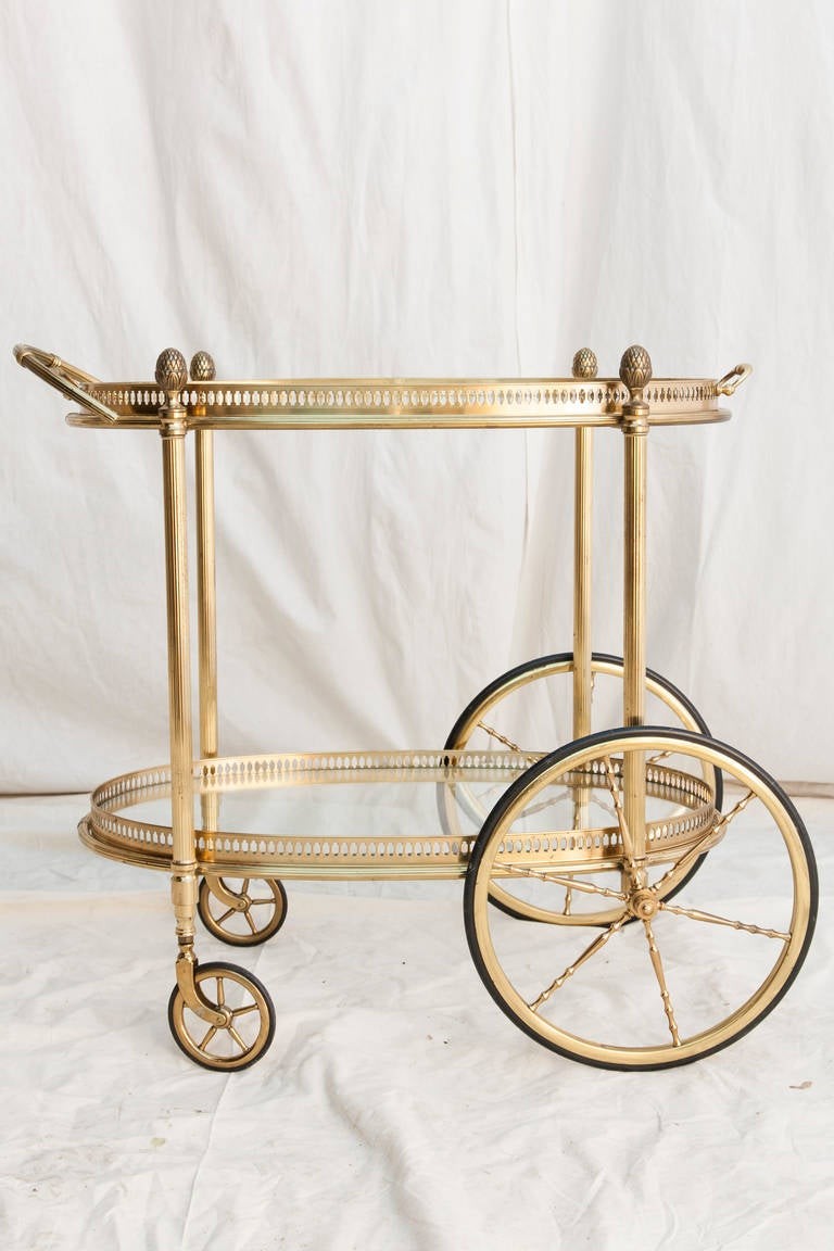 This mid twentieth century oval brass bar cart from France features a brass gallery around each of its glass shelves.  Its top shelf is a removable tray, and its four legs are capped with Louis XVI pine cone finials.   An elegant and charming piece