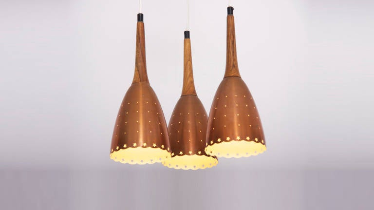 Impressive copper chandelier with performated shades and tropic wood details. Scandinavian made. Hanging height of the shades can be changed in any wanted position. Beautiful piece of Scandinavian lighting in nearly mint condition. Shades are 37 cm