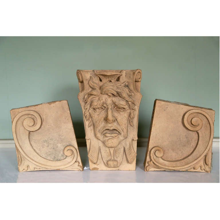 An artificial stone keystone depicting Tragedy, modelled in high relief, flanked by two further elements modelled with c-scrolls.  Keystone dimensions: h 49.5cm, w 31.5cm, d 37.5cm C-Scroll dimensions: h 35.5cm, w 34.5cm, d 13.5cm  Available to