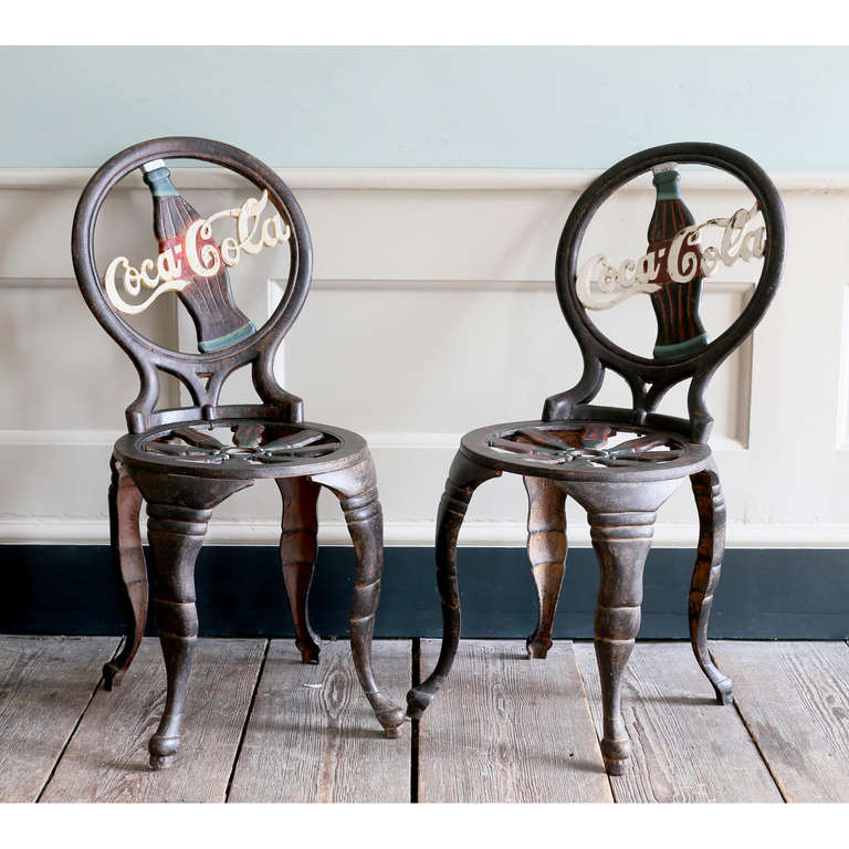 A rare pair of 'Coca-Cola' cast iron chairs, c.1950, the back inset with iconographic bottle and logo, on modified cabriole legs.  Available to view at Brunswick House, London.
