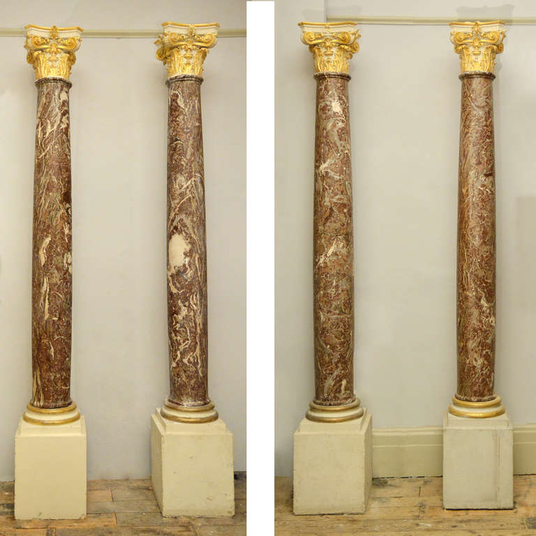 A set of four Flemish columns, in highly figured Rouge Royale marble, each surmounted by parcel-gilt plaster capital, on stepped Portland stone plinth bases.  Ex. 3 Carlton Gardens, St. James, London.  Available to view at Brunswick House,