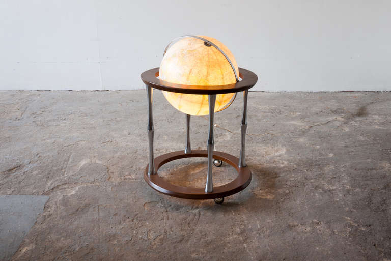 This floor globe by Replogle floats within a ring of walnut, supported by four 'turned' chrome stiles, which connect to a base of walnut. The globe rotates, spins and lights from within.