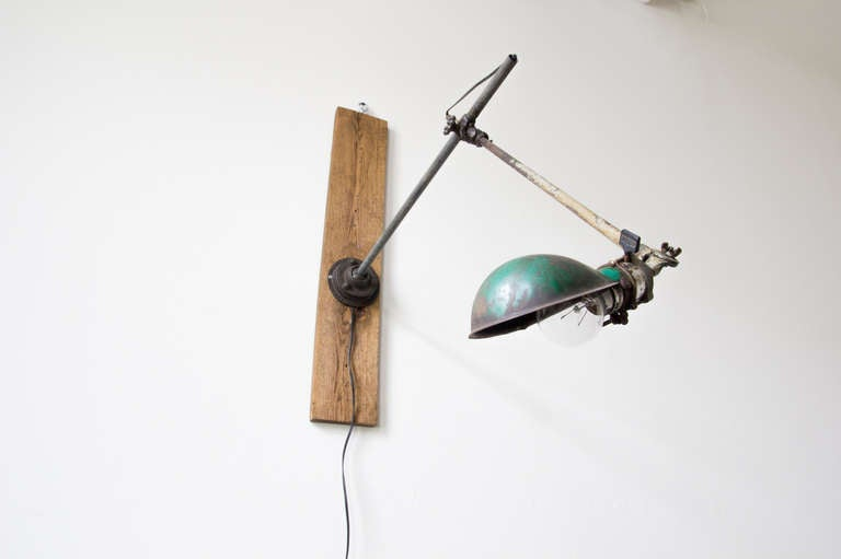 An adjustable wall-mounted task lamp by O.C. White with green enamel shade. The boom arm slides along the mounted rod, as well as extends and retracts.