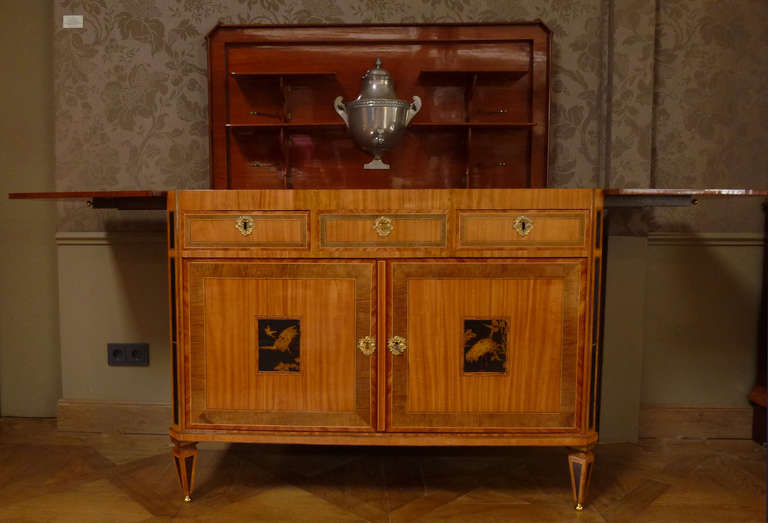 Overall inlaid with various bands, canted rectangular hinged top opening to two hinged shelves, enclosing a removable zinc liner and foutain and two hinged shelves to each side, two drawers and two doors below, each centred by a lacquer panel