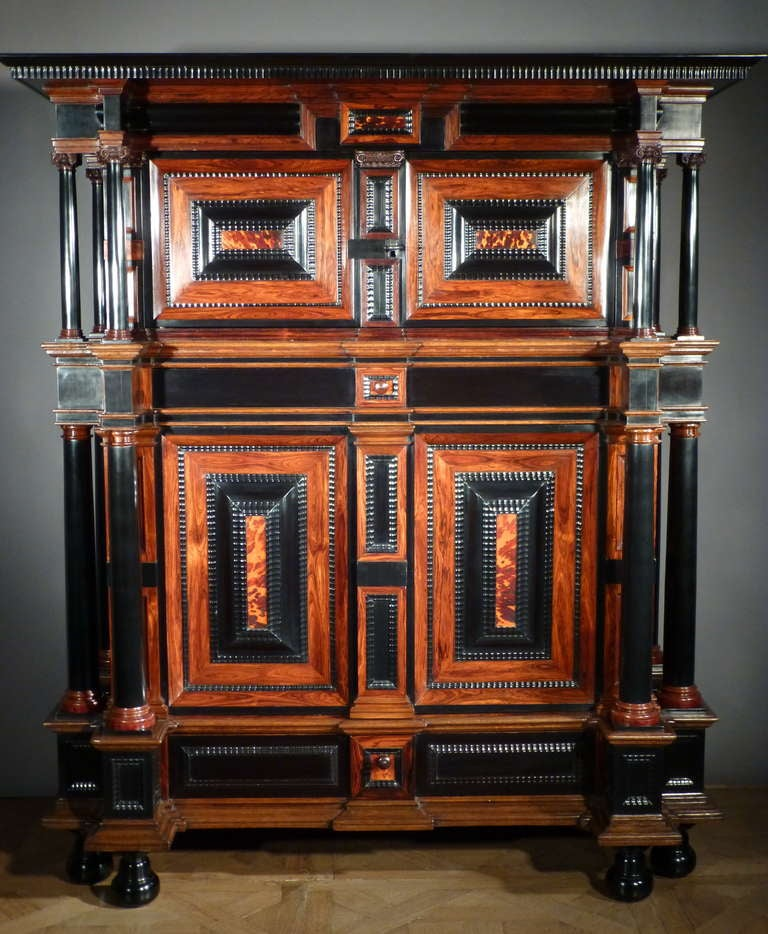 The oversailing cornice  above a pair of panelled doors enclosing an interior with two shelves flanked by six massive tapering ebony columns with carved Corinthian capitals. Below a pair of conforming doors, the raised panels veneered with rosewood