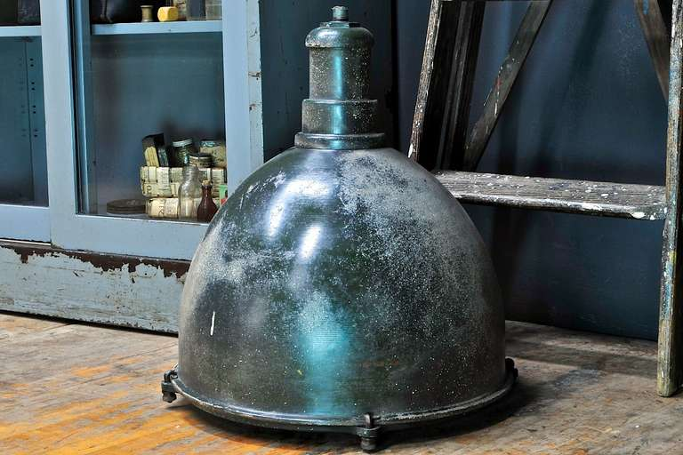 Extra large glass lensed pendant lights, with original (as-found) wear to surfaces, just cleaned and waxed. Overall green exterior steel, paint specks or residue, patina varies. Quantity available.  Multiple metals; cast iron, enameled spun or