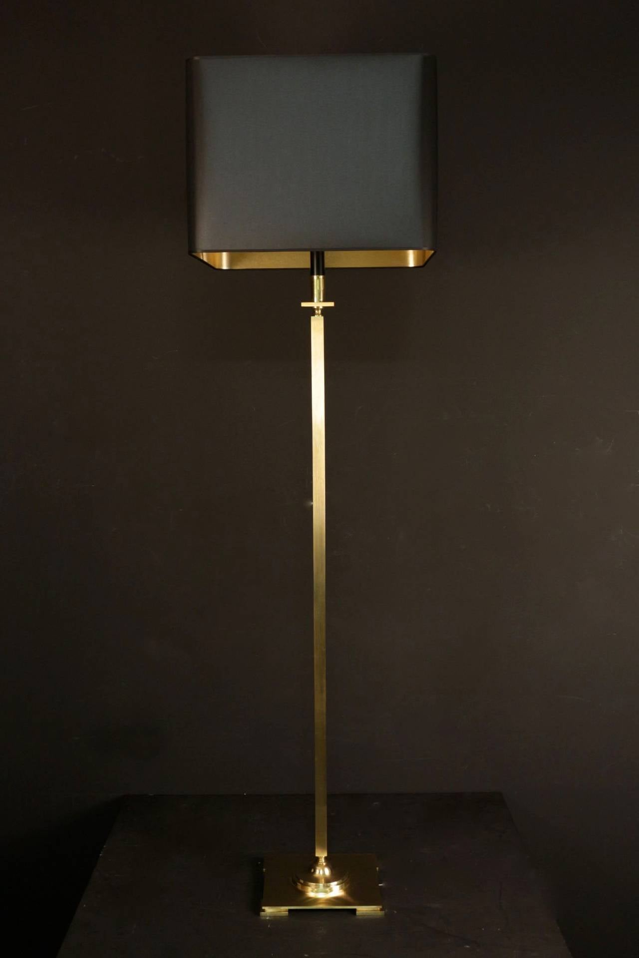 1960s floor lamp by Maison Jansen in gilded brass and blackened brass on the top part. New tailored lam shade with black outside and gilded inside.  Two lighted arms.
