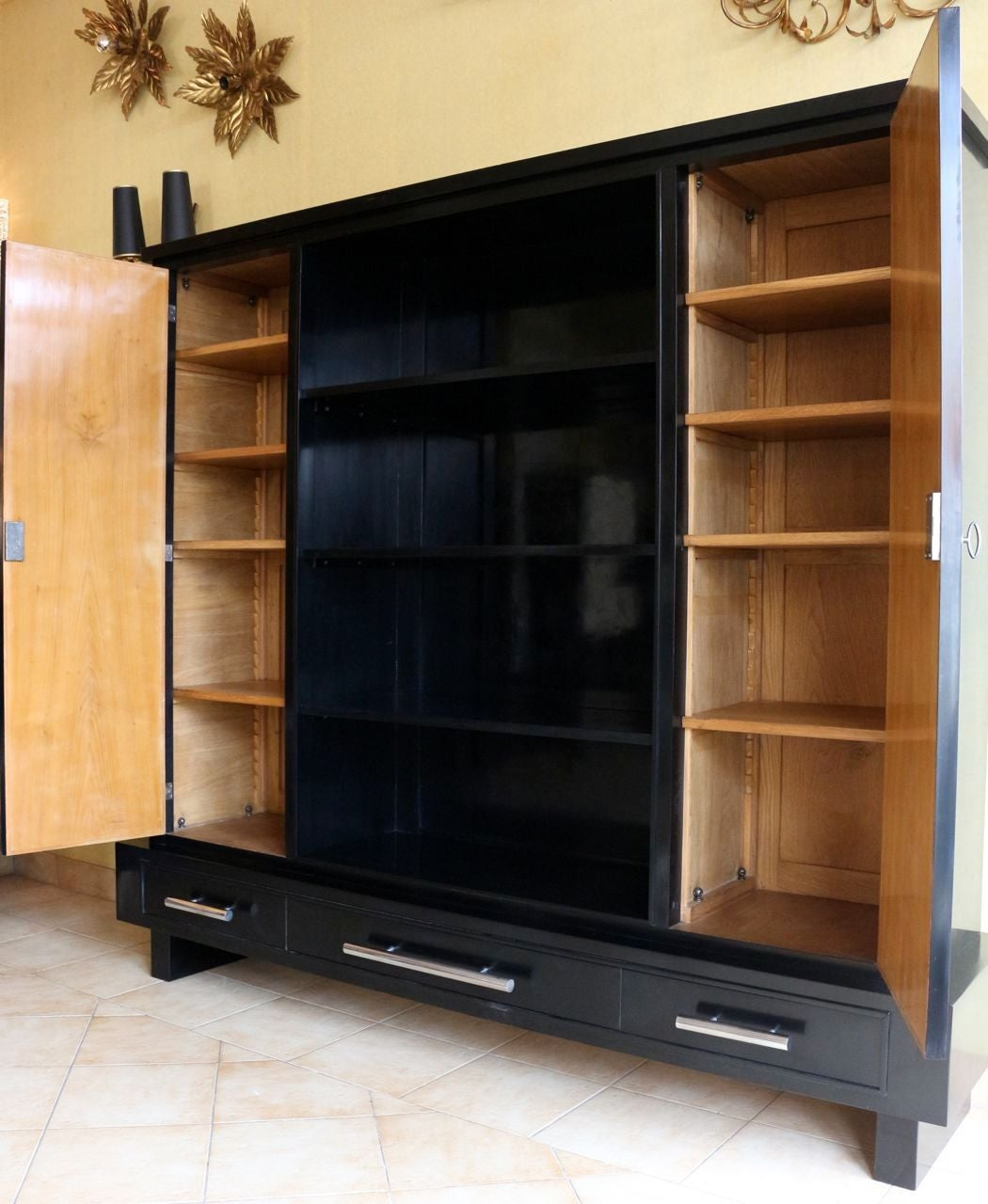 1940s bookcase by Rene Gabriel in black waxed lacquer, consisting of two doors, black lacquer exterior and mahogany inside with shelves. Set of three large shelves in the center.