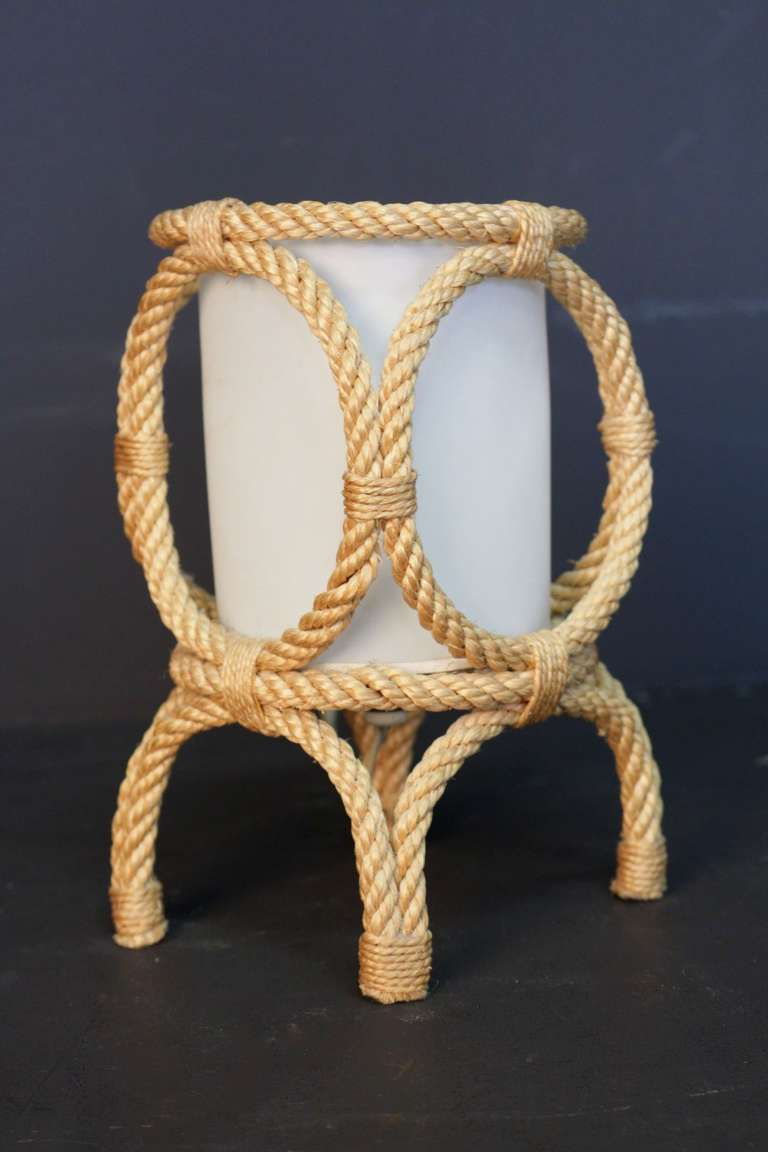 1950's rope lantern table lamp by Adrien Audoux and Frida Minet mounted on four feet and adorned with four circles.  Cylindrical shade. One bulb.