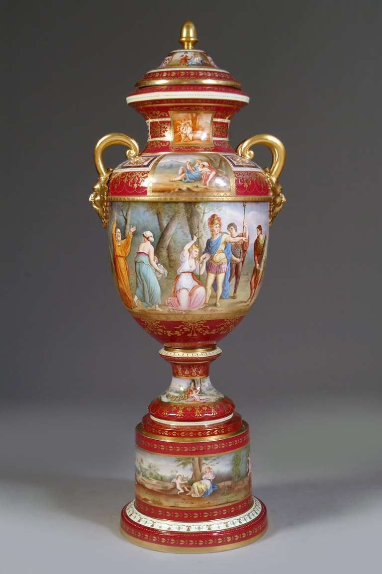 This magnificent large Royal Vienna style porcelain covered urn is Surmounted by domed cover with acorn finial and flanked by satyr mask handles, centered by a panel depicting scenes of the life of Alexander, on circular foot and conforming Stand,