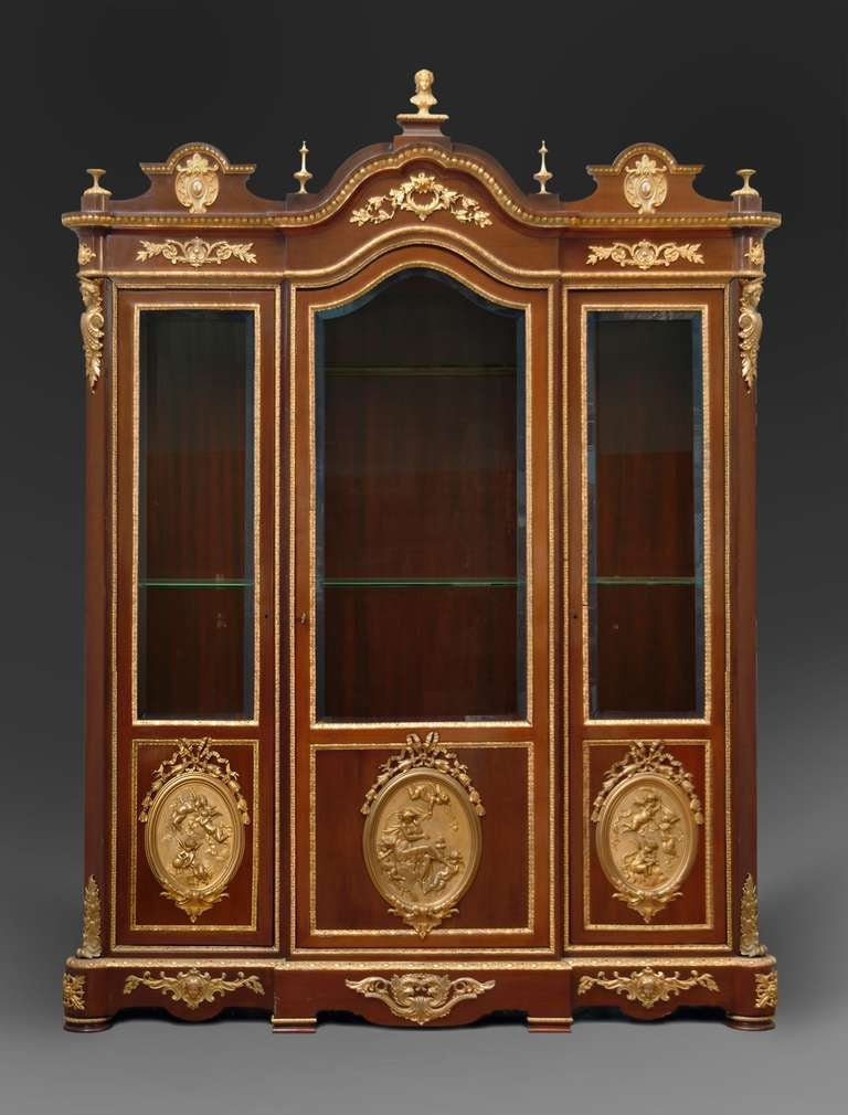 A spectacular 19th century French gilt-bronze mounted vitrine by: CHARLES-GUILLAUME DIEHL, PARIS, and Leon Bertaux. Each door with a relief-cast oval plaque showing putti in various positions , inscribed: Mme Leon BERTAUX. The lock-plate signed