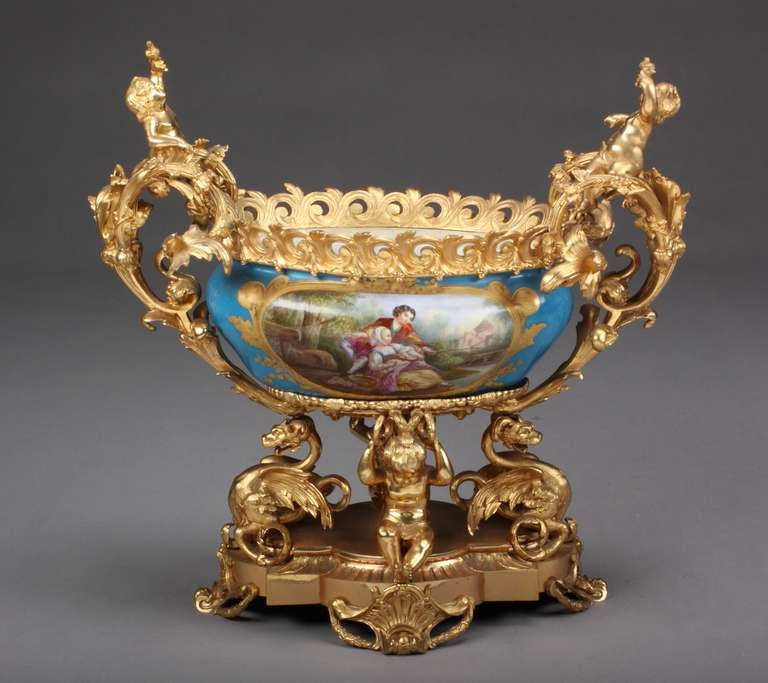 A very fine and unusual French Sevres porcelain gilt-bronze mounted figural centerpiece. Having two molded cherubs holding birds on the handles of the masterfully painted porcelain bowl supported by two dragons and two sitting cherubs on a base.