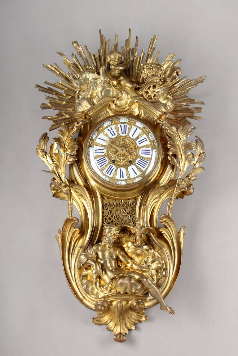 A large French Louis XV style gilt bronze cartel clock. After the model by Jacques Caffièri. The cartouche-shaped case representing sunrise and sunset, surmounted by a putto and doves in the Venus' chariot above clouds in front of a large sunburst.