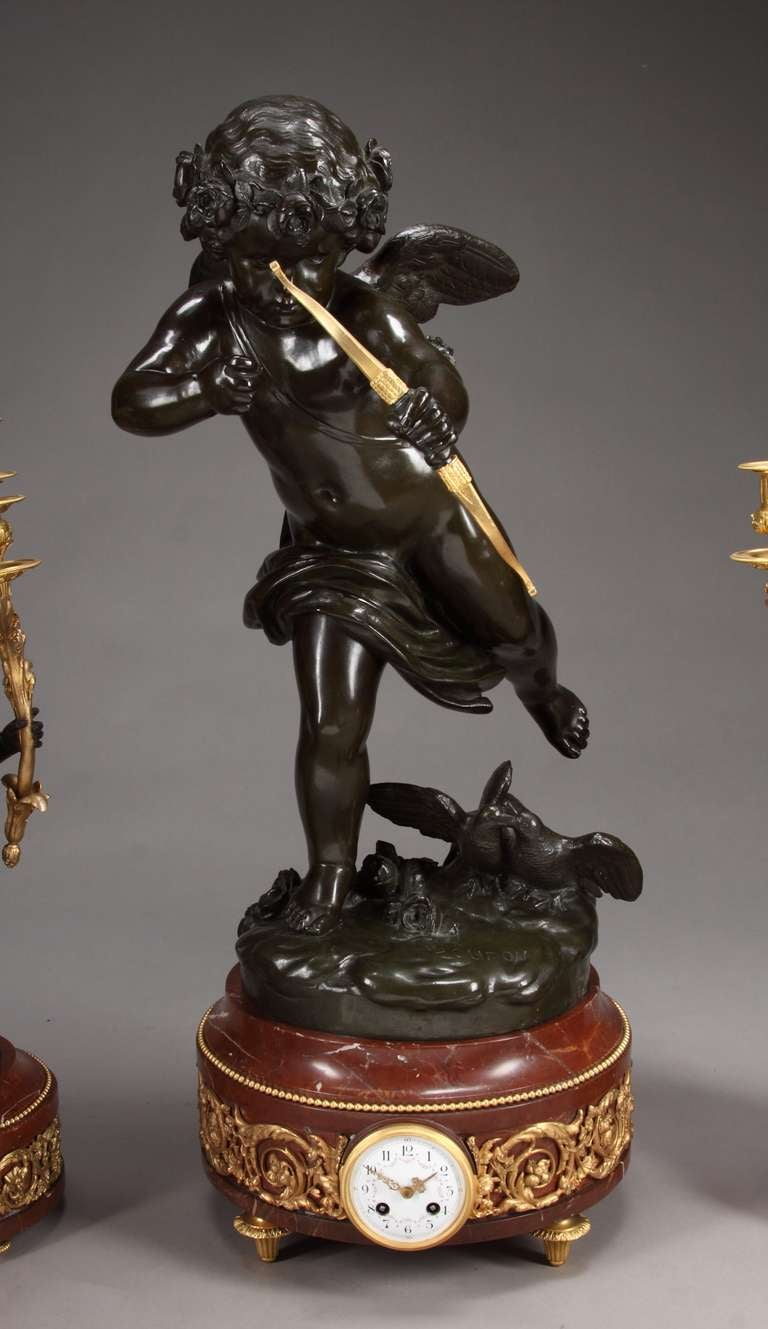 An exceptional large 19th century French figural clock set after a model by Jean Antoine Houdon. Mounted with a large bronze model of a cupid holding a gilt bow and arrow, upon a naturalistic base with flowers and doves, supported on a rouge marble