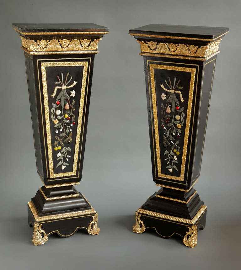 A Pair of Antique Italian Pietra Dura & Gilt Bronze Mounted Pedestals   Italy, Circa 1880  Each with a rectangular top above a tapering ebony wood body, on a rectangular plinth. The central panels decorated with a display of hard stone inlays