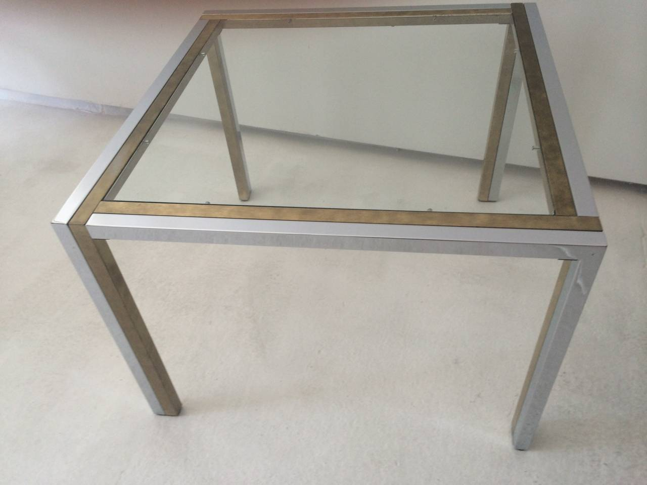 Most unique French table by Maison Jansen, 1970s.  Two-tone combination of brass and chrome with glass top.