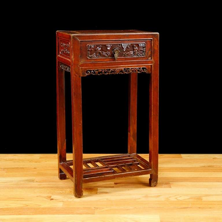 Qing table in elm with original Cinnabar lacquer, one drawer with carved fascia in relief of two figures in landscape, with carved side panels and spandrels, China, circa late 1700s. Measures: 17 1/2