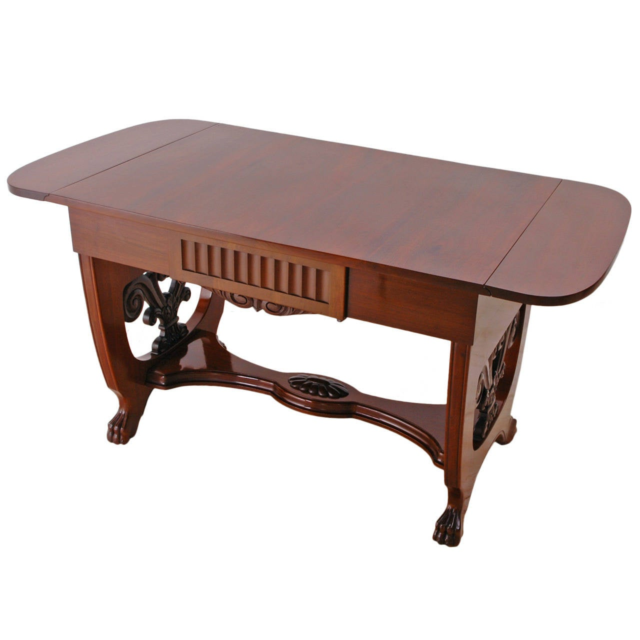 A very fine Baltic writing or sofa table in the Empire style (and edging toward the Art Deco period that would follow.) In Cuban mahogany with carved trestle-base ending in carved lion's paw feet. Features two drop-leaves and one-drawer. French