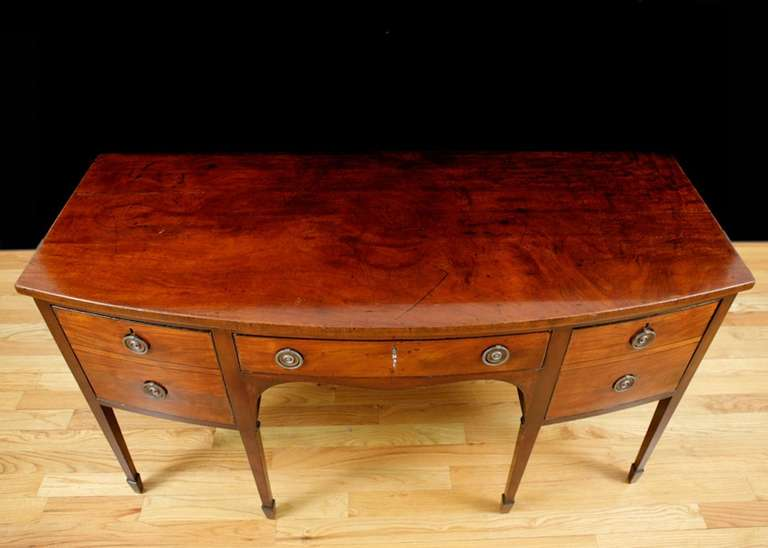 A handsome George III sideboard in mahogany with bowed front and square tapered legs ending in spade feet, with central frieze drawer flanked by two cellarette drawers. Top is composed of a single solid plank of mahogany, England, circa